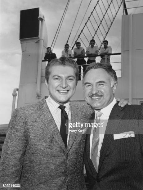 American pianist and singer Liberace born Wladziu Valentino Liberace with his brother George on the deck of the 'Queen Mary' during his tour of...
