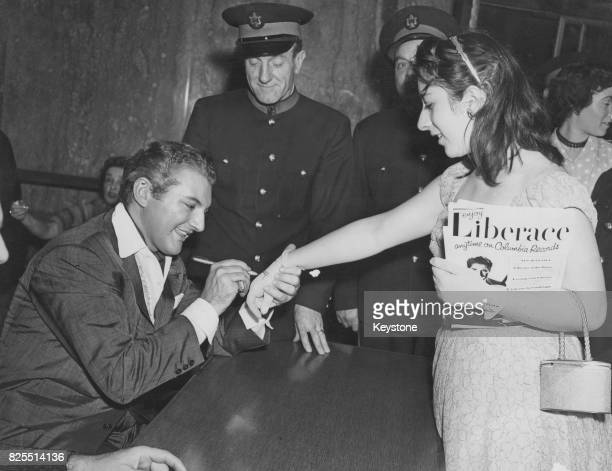 American pianist and singer Liberace born Wladziu Valentino Liberace autographs the glove of an admirer at the Royal Festival Hall London 1st October...