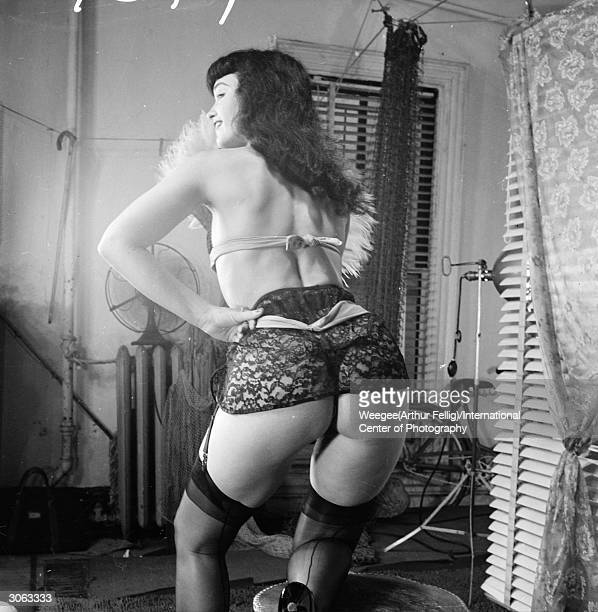 American pinup Bettie Page Playboy playmate of the month for January 1955 poses in a suspender belt 1950s Photo by Weegee/International Center of...
