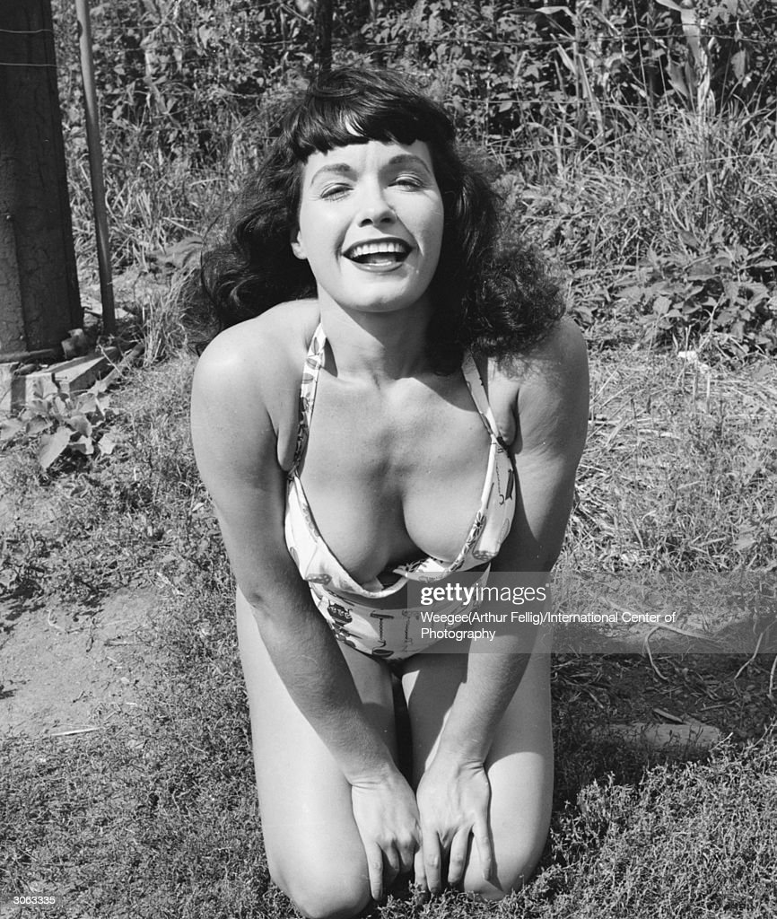 American pin-up <a gi-track='captionPersonalityLinkClicked' href=/galleries/search?phrase=Bettie+Page&family=editorial&specificpeople=216044 ng-click='$event.stopPropagation()'>Bettie Page</a>, Playboy playmate of the month for January 1955 shows off her cleavage in a bikini, New York state, 1956. (Photo by Weegee(Arthur Fellig)/International Center of Photography/Getty Images)