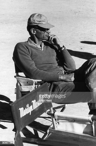American playwright Arthur Miller resting on the location shoot of 'The Misfits' in the Nevada Desert Next to him is the chair designated for his...