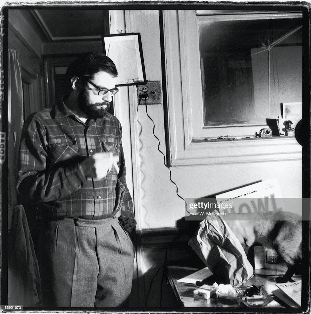 American poet Allen Ginsberg (1926 - 1997) stands in his apartment (170 East 2nd Street) and eyes at his pet Siamese cat who stands on table, New York, New York, Januray 9, 1960. (Photo by Fred W. McDarrah/Getty Images