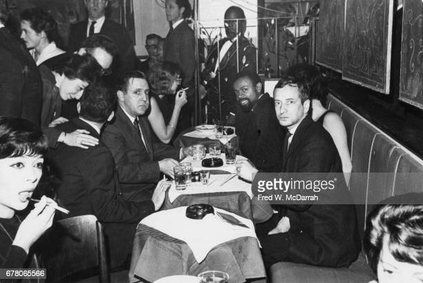 American poet and playwright LeRoi Jones and 8th Street Bookshop owner Ted Wilentz sit with unidentified others during a Grove Press event held at...