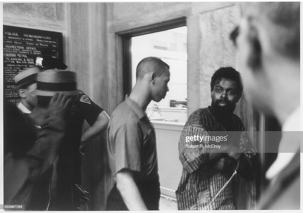 American poet and playwright LeRoi Jones (later known as Amiri Baraka) (1934 - 2014) (with beard) in a police station, bloodied and in chains after being arrested during a riot, Newark, New Jersey, July 14, 1967. Jones had been arrested for allegedly carrying concealled weapons and was beaten while in custody; he was convicted of the crime, but the conviction was later overturned. The Newark riots lasted 5 days and resulted in 26 deaths and millions of dollars in property damage.