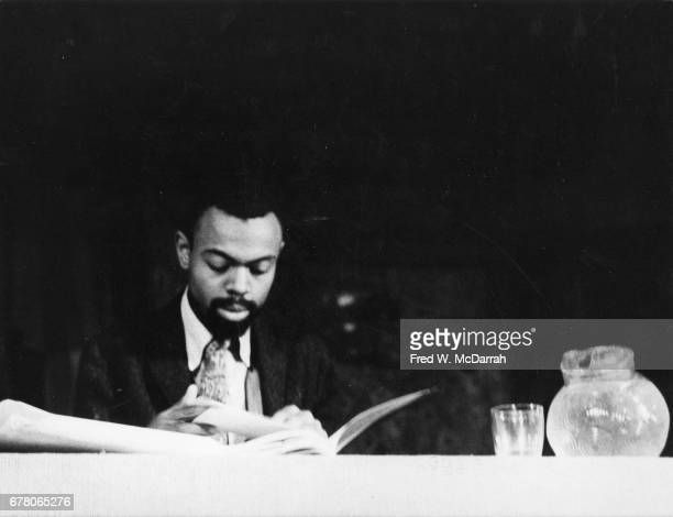 American poet and playwright LeRoi Jones reads as he sits at a table during a benefit for Yugen Press at the Living Theatre New York New York...