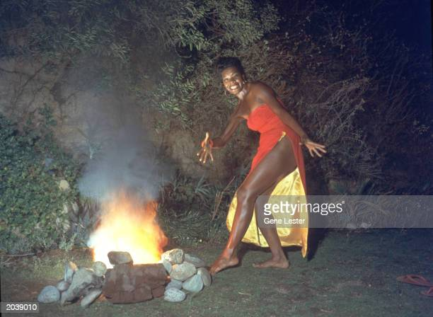American poet and singer Maya Angelou wears a red dress while dancing next to a fire in a promotional portrait taken for the cover of her album 'Miss...