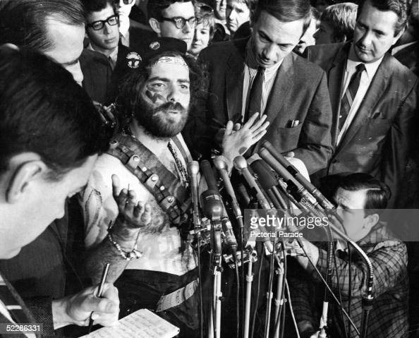 American political activist Jerry Rubin addresses reporters from behind a bank of microphones while dressed in a camouflage paint and a bandolier...