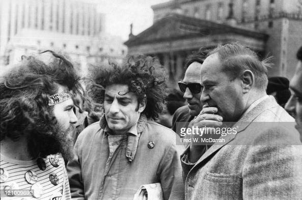 American political and social activists Jerry Rubin and Abbie Hoffman talk with unidentified others on a street New York New York March 22 1969