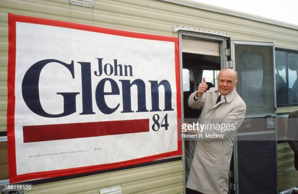 American politician and former astronaut Senator John Glenn gives a 'thumbs up' sign as he leans out of the door during his campaign for the...