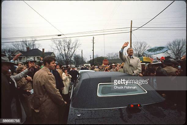 American politician and former US President Jimmy Carter waves from a car upon his return to his hometown after leaving the White House Plains...