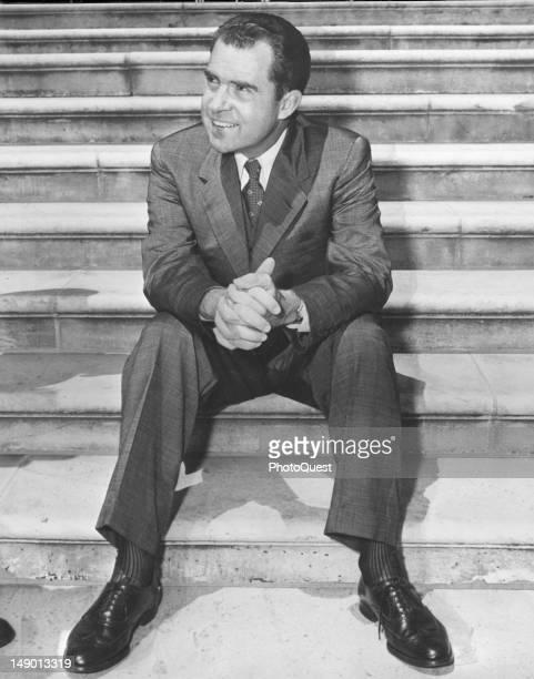American politician and US Vice President Richard Nixon smiles as he sits on the steps of the Senate Washington DC 1956