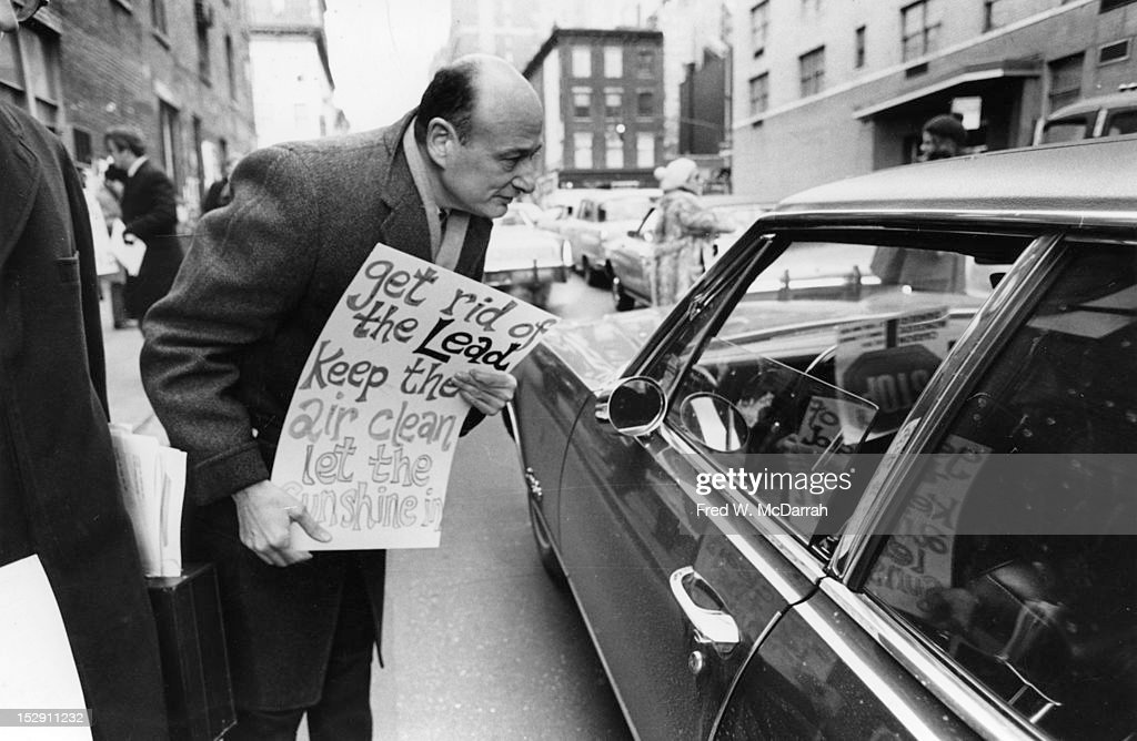 American politician (and future New York City Mayor) Ed Koch leans over to speak to a motorist in a car near the entrance to the Midtown Tunnel, New York, New York, February 13, 1970. Koch carries a sign that reads 'Get Rid of the Lead, Keep the Air Clean, Let the Sunshine In.'