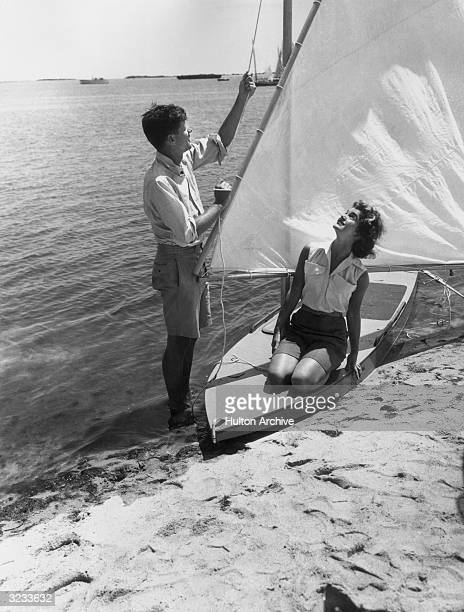 American politician John F Kennedy stands at the water's edge hoisting the sail of a small boat upon which kneels his wife Jacqueline Bouvier Kennedy...