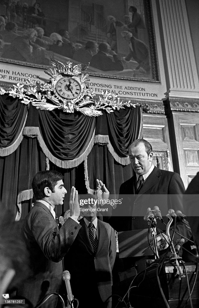 American politician MIchael Dukakis (left) takes an oath as he sworn in as the 65th Governor of Massachusetts by State Senate President Kevin Harrington, Boston, Massachusetts, 1975.