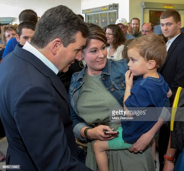 American politician US Senator Ted Cruz speaks with Kelly Ramseyer and her son Branson at a campaign rally in support of fellow Republican Ron Estes'...