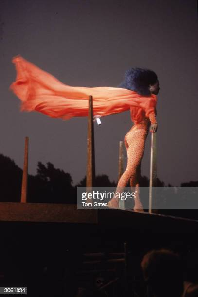 American pop and RB singer Diana Ross performs on stage in her Central Park concert wearing tights with an orange cape blowing behind her New York...