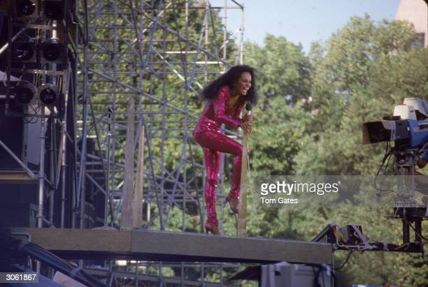 American pop and RB singer Diana Ross performs on stage in her Central Park concert wearing a violet sequined jumpsuit New York City July 22 1983