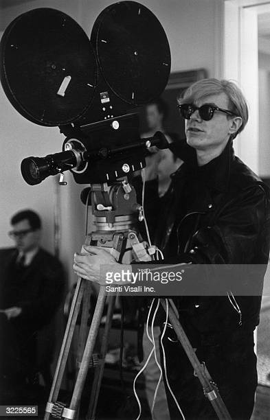 American pop artist and filmmaker Andy Warhol stands behind a movie camera while filming the movie 'Snow White and the Seven Dwarfs'