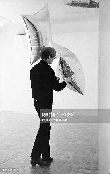 American pop artist Andy Warhol arranges his 'Silver Clouds' installation at the Leo Castelli Gallery New York New York April 1 1966 The mylar...