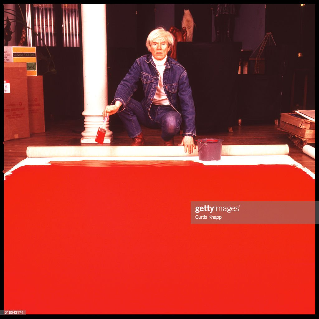 American Pop artist Andy Warhol (1928 - 1987) paints a red canvas on the floor of his studio, the Factory, New York, New York, January 14, 1983.