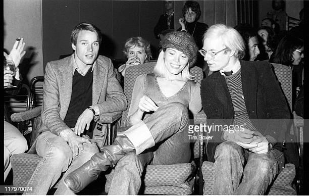 American Pop artist Andy Warhol speaks to French singer and actress Andrea Lear at the premiere of 'Shampoo' at the Columbia Pictures Screening Room...