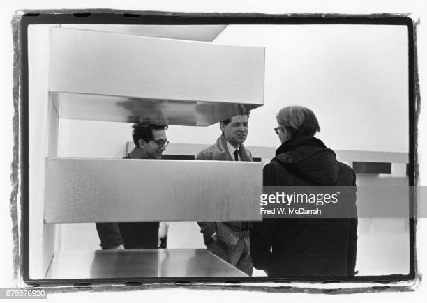 American Pop artist Andy Warhol speaks with fellow artist Frank Stella and an unidentified man during an exhibition of Donald Judd's work at the...