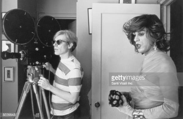 American pop artist Andy Warhol stands behind a movie camera next to actor Mario Montez dressed as a woman on the set of his film 'Chelsea Girls' New...