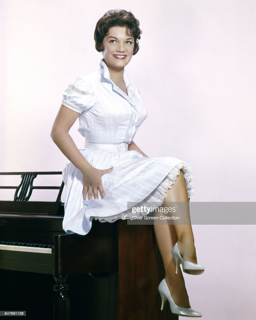 American pop singe Connie Francis sits on a piano, circa 1965.