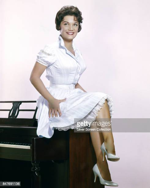 American pop singe Connie Francis sits on a piano circa 1965