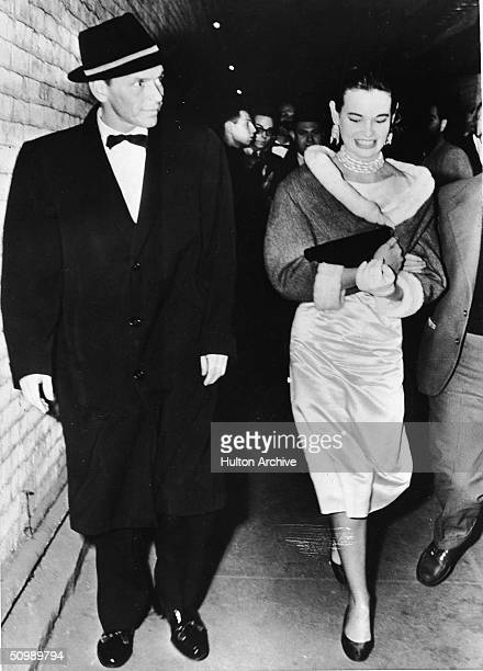 American pop singer and actor Frank Sinatra in an overcoat and hat walks next to American heiress and designer Gloria Vanderbilt as she wears a...