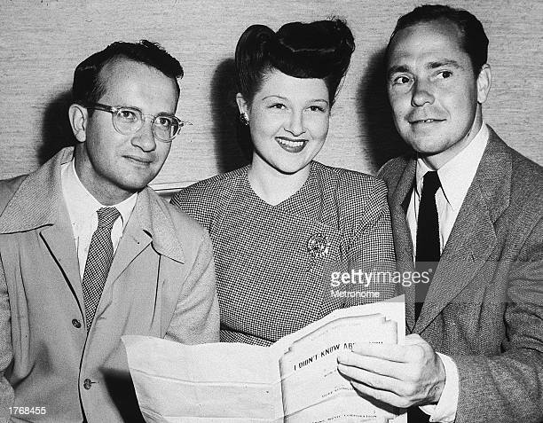American pop singer and songwriter Johnny Mercer conductor and arranger Paul Weston and singer Jo Stafford pose together while holding sheet music c...
