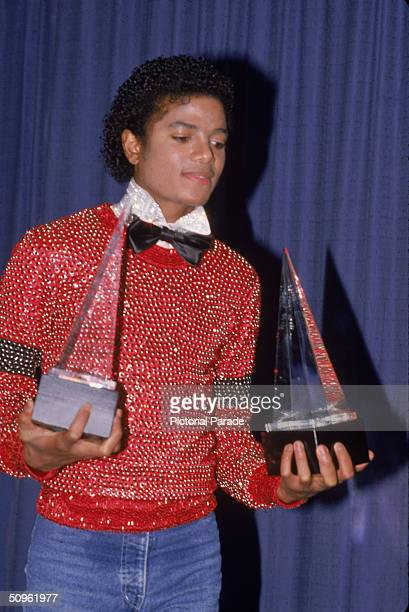 American pop singer Michael Jackson carries the two American Music Awards he won for his album 'Off the Wall' they are for Favorite Male Vocalist...