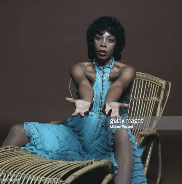 American pop soul and disco singer and songwriter Donna Summer posed sitting on a cane lounger chair wearing a long blue summer dress London 29th...