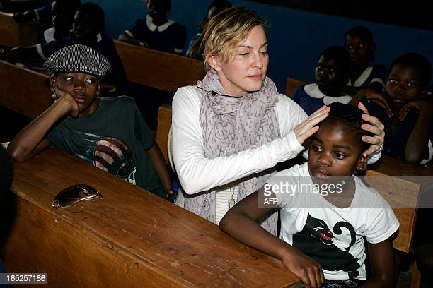 American pop star Madonna sits on April 2 2013 with the two children she adopted in Malawi David Banda and Mercy James in a classroom of the Mkoko...