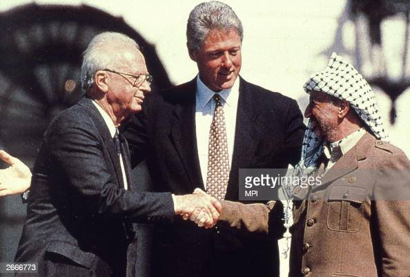 American President Bill Clinton watches as the Israeli Prime Minister Yitzhak Rabin shakes hands with the Palestinian leader Yasser Arafat in the...