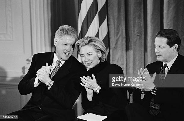 American President Bill Clinton whispers to his wife First Lady Hillary Clinton as they and Vice President Al Gore applaud at an unidentified event...