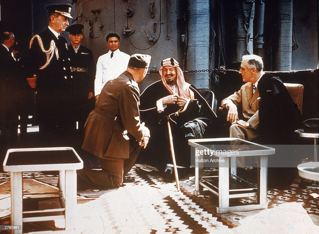 American president Franklin Delano Roosevelt (R, 1882 -1945) meets with King Ibn Saud (1880- 1953) of Saudi Arabia, chief of staff William D. Leahy (on knee, 1875 - 1959) and Col. William A. Eddy (to Leahy's right, 1896 - 1962), minister to Saudi Arabia aboard a United States warship, February 20, 1945.