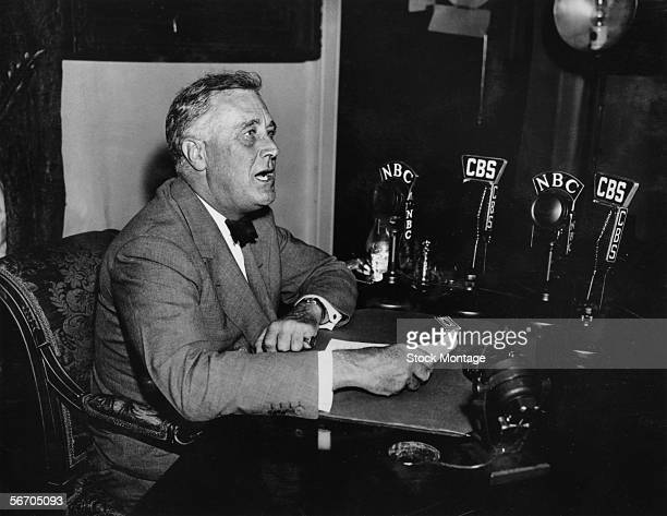 American President Franklin Delano Roosevelt sits at a desk in front of a series of microphones as he delivers a 'Fireside Chat' radio broadcast 1930s