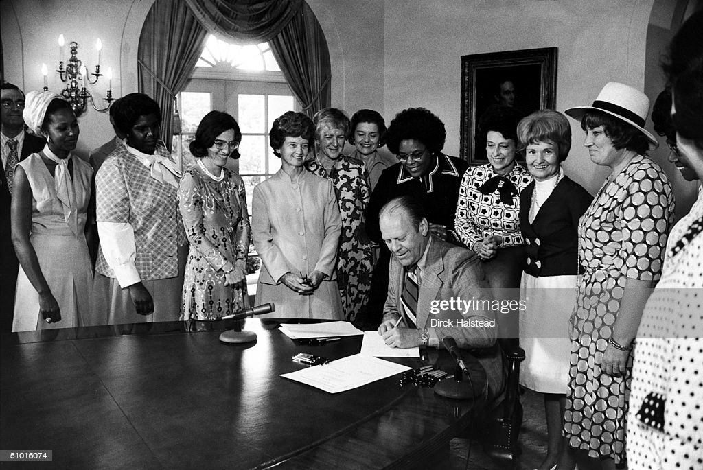 American President Gerald Ford signs legislation declaring August 26th Women's Equality Day, Washington DC, August 22, 1974. Also present are, from left, unidentified man, U.S. Representatives Yvonne Burke, Barbara Jordan (1936 - 1996), Elizabeth Holtzman, Marjorie Holt, and Leonor Sullivan (1902 - 1988), First Lady Betty Ford, and U.S. Representatives Cardiss Collins, Corinne Boggs, Margaret Heckler, Bella Abzug (1920-98), and Shirley Chisholm.
