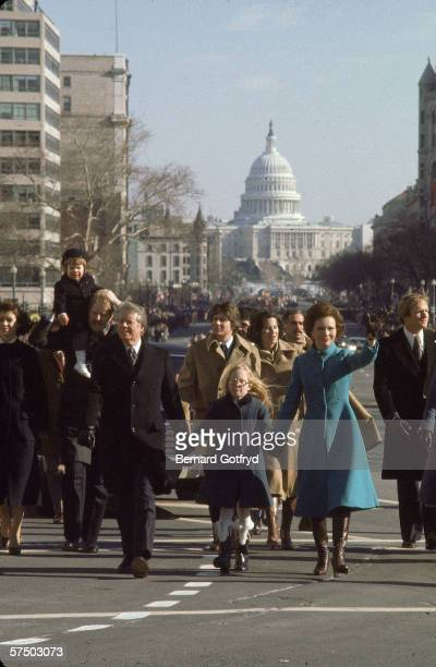 American President Jimmy Carter hand in hand with his daughter Amy Carter and his wife Rosalynn Carter walks along the street during his inaugural...