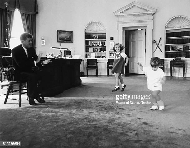 American President John F Kennedy claping while watching his daughter Caroline and son John Jr dance in the Oval Office