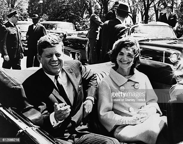 American President John F Kennedy with his wife Jacqueline Lee 'Jackie' Bouvier as they ride in a convertible between Blair House and the White House...