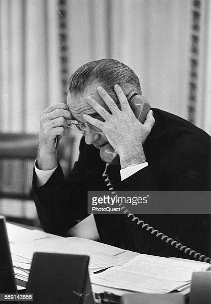American President Lyndon Johnson talks on the telephone at his desk in the White House Washington DC 1964