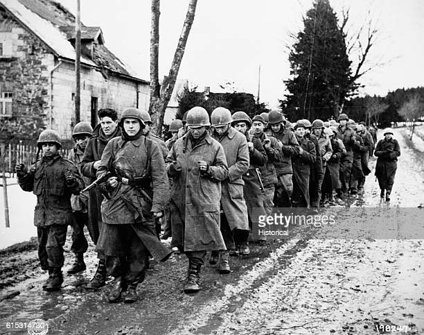 American prisoners captured during the Battle of the Bulge march under guard by German soldiers Dec 17 1944