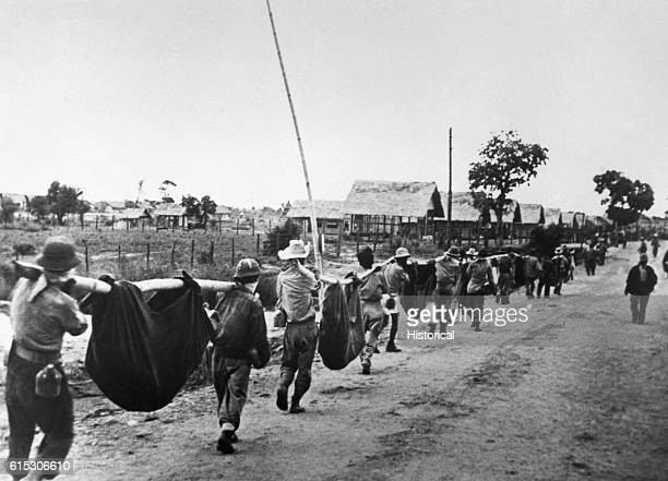 American prisoners use improvised litters to carry their comrades who from the lack of food or water on the march from Bataan fell along the road...