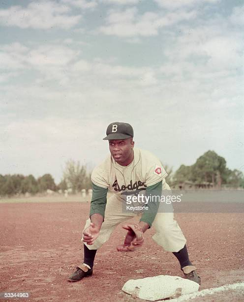 American professional baseball player Jackie Robinson of the Brooklyn Dodgers dressed in a road uniform crouches by the base and prepares to catch a...