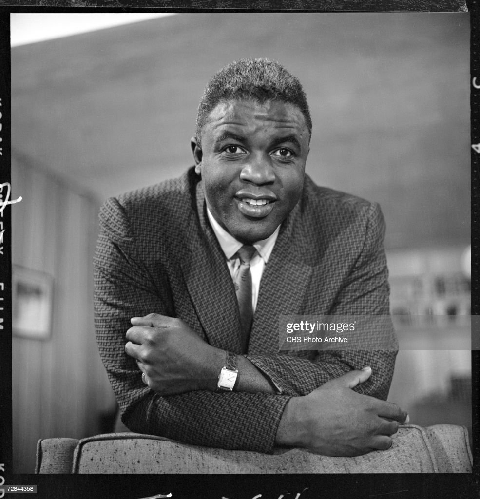 American professional baseball player <a gi-track='captionPersonalityLinkClicked' href=/galleries/search?phrase=Jackie+Robinson&family=editorial&specificpeople=93570 ng-click='$event.stopPropagation()'>Jackie Robinson</a> (1919 - 1972), who famously broke the Major League Baseball color barrier in 1947 leans on the back of a chair as he appears at his home for the CBS television program 'Person to Person' shortly after announcing his retirement from baseball, Stamford, Connecticut, January 21, 1957.