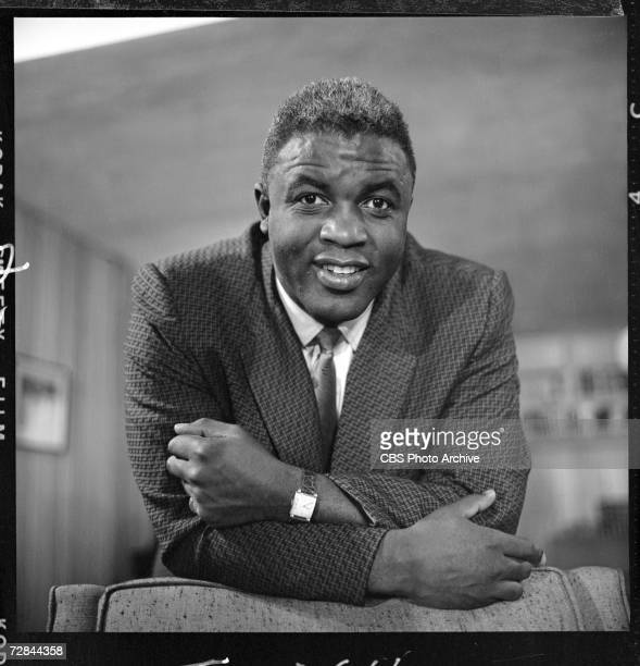 American professional baseball player Jackie Robinson who famously broke the Major League Baseball color barrier in 1947 leans on the back of a chair...