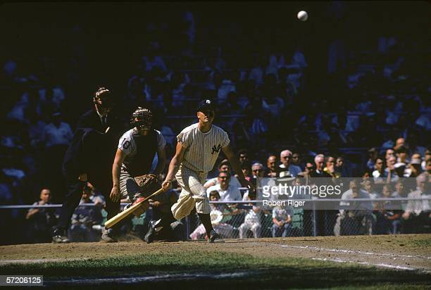 American professional baseball player Roger Maris of the New York Yankees prepares to take off for first base after making a hit at home plate during...