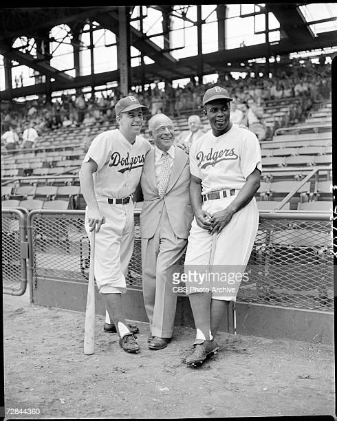 American professional baseball players Pee Wee Reese and Jackie Robinson who famously broke the Major League Baseball color barrier in 1947 pose for...